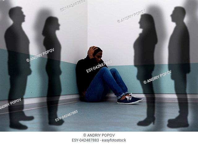 Shadows Of People Standing Near Scared Man Sitting On Floor