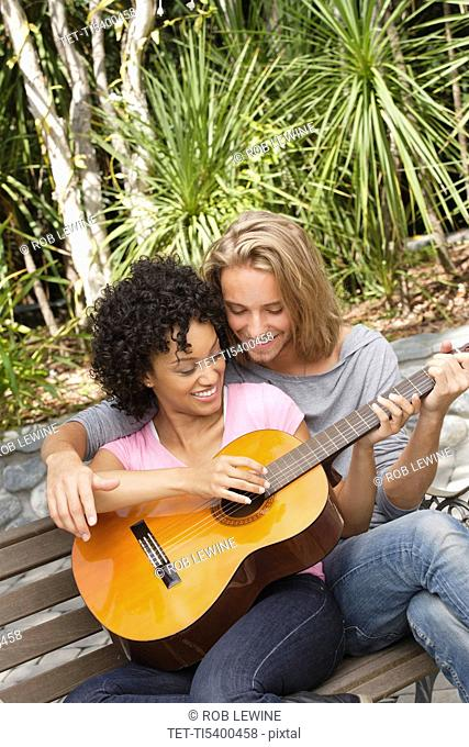 Young couple in park, woman playing guitar