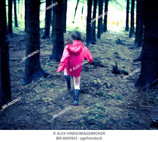 Young girl in pink coat running towards light out of forest, United Kingdom
