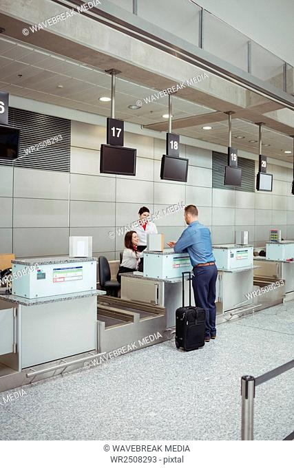 Airline check-in attendant handing passport to passenger