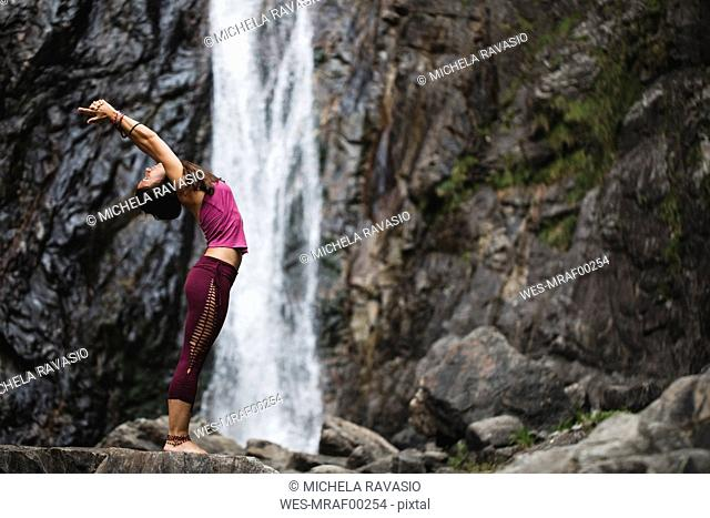Italy, Lecco, woman doing Standing Backbend Yoga Pose on a rock near a waterfall