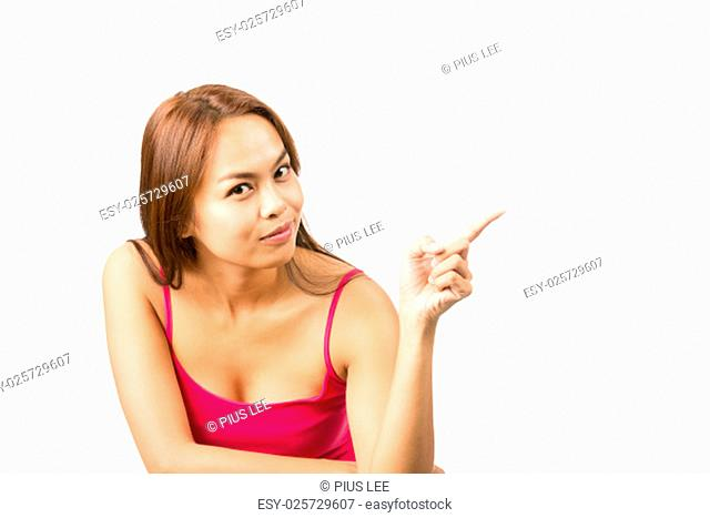 Gorgeous Asian woman in pink sleeveless shirt casually finger pointing at blank advertisement copy space, showing object to be inserted while looking at camera