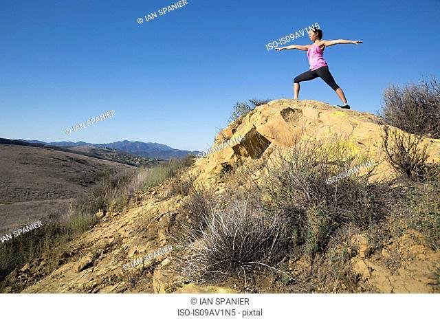 Mature female practicing yoga pose on hill, Thousand Oaks, California, USA