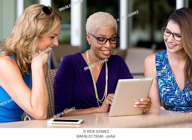 Businesswomen using digital tablet at table