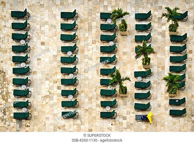 USA, Hawaii, Honolulu, Green lounge chairs lined up in columns and rows adjacent to hotel swimming
