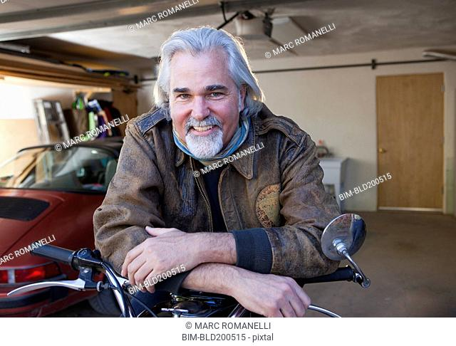 Caucasian man in garage with motorcycle