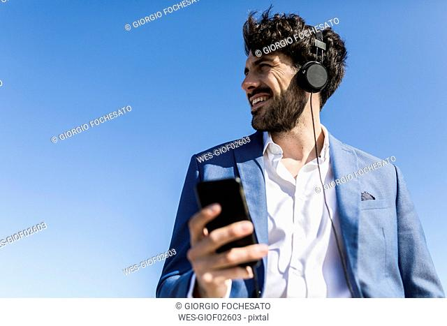 Young businessman with smartphone wearing headphones under blue sky