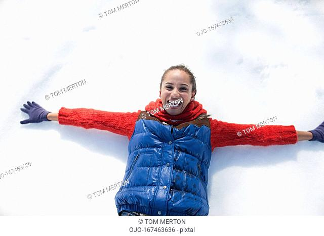Smiling woman making snow angels
