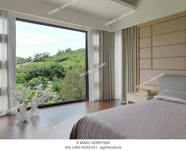 Modern bedroom with view of foliage