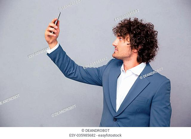 Portrait of a handsome businessman making selfie photo over gray background