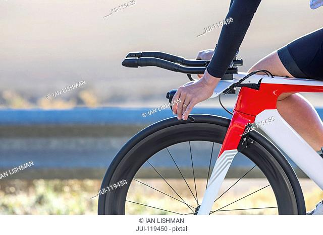 Close-up of female cyclist hands on handlebars of race bicycle