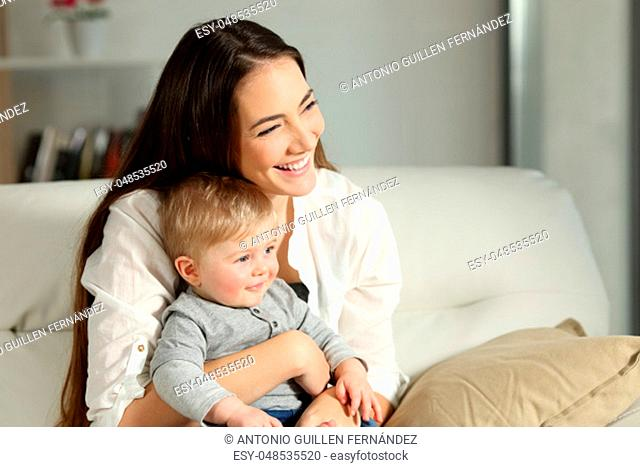 Happy woman and son looking away sitting on a couch in the living room at home