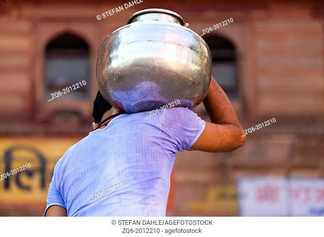 Man carrying Metal Container in Varanasi, India
