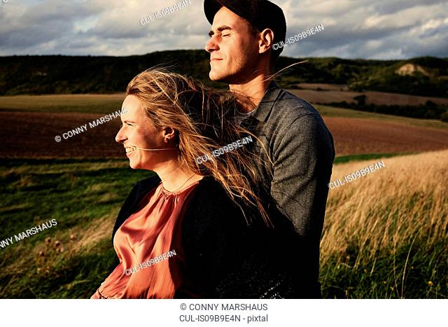 Pregnant mid adult couple on windy hillside