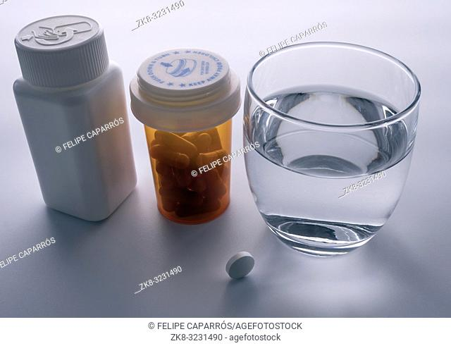 Several bottles with diverse medication next to a glass of water, conceptual image