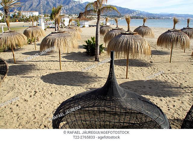 Puerto Banus (Marbella) Spain. Beach umbrellas next to the marina of Puerto Banus in Marbella town