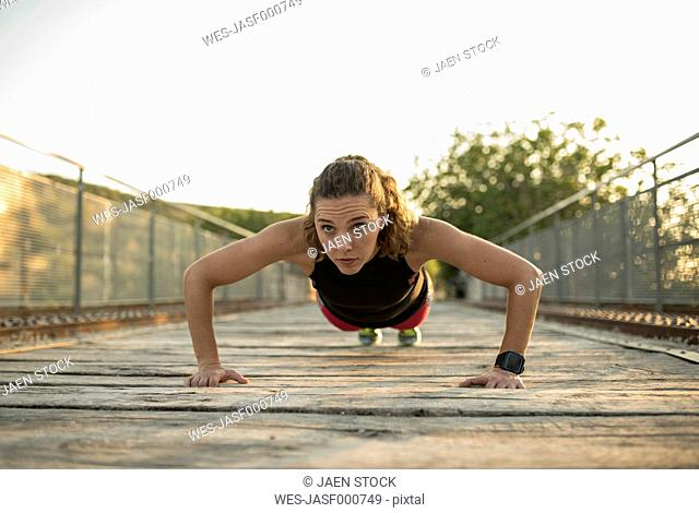 Woman doing pushups on a bridge