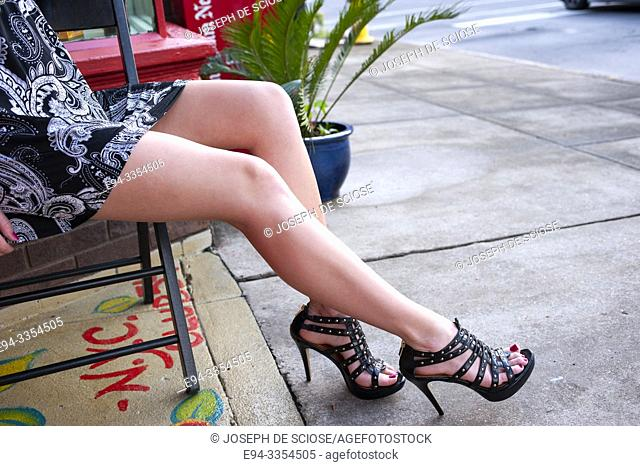 Partial view of a woman's long, bare legs seated near a sidewalk