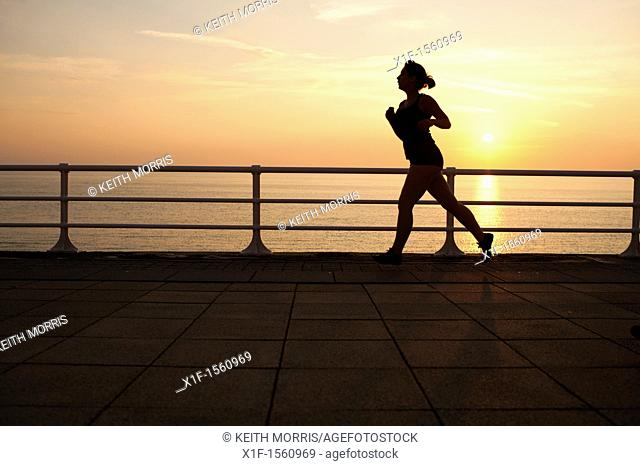 a woman jogger at dusk on a warm september evening aberystwyth promenade wales uk