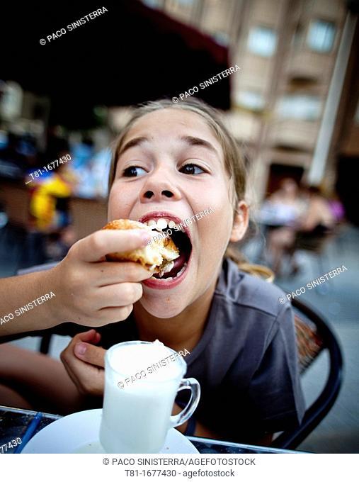 Girl eating in an outdoor café