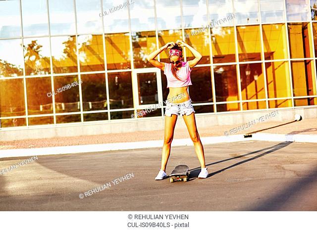 Young woman standing road, fixing hair, skateboard between feet