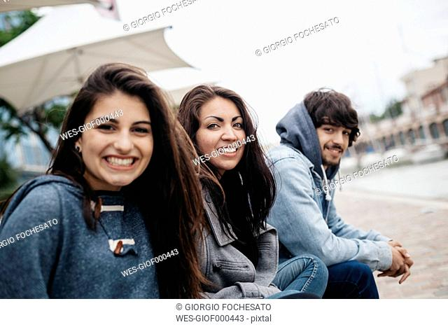 Italy, Rimini, portrait of three happy friends outdoors