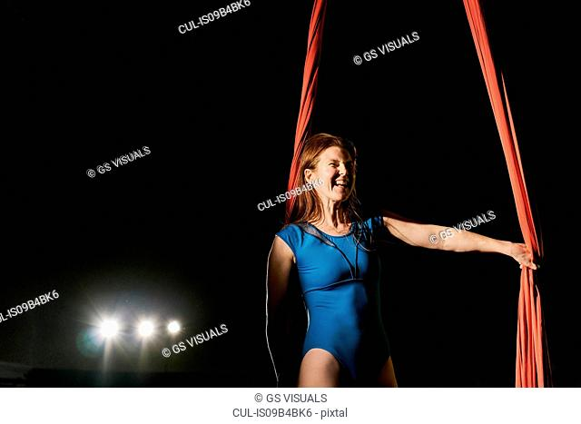 Young female aerial acrobat laughing by red silk rope