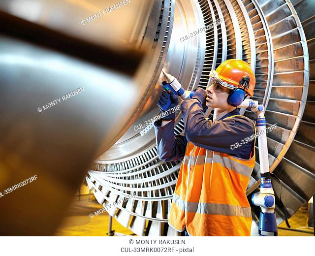 Worker inspects turbine in power station