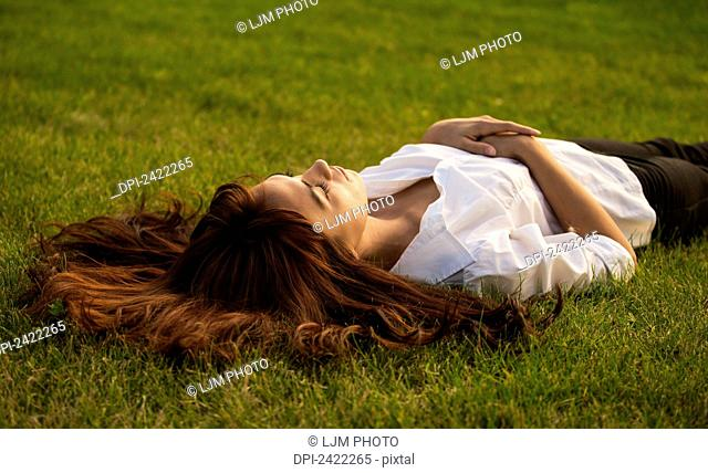 Portrait of a young woman with long red hair laying in the grass; Edmonton, Alberta, Canada