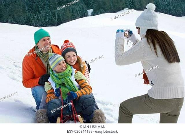Mother taking picture of family sitting on ski slope