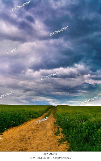 Field path with dramatical storm clouds in the background