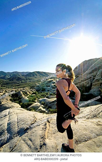 A woman stretches before running at Piedra Blanca, Sespe Wilderness, Los Padres National Forest California