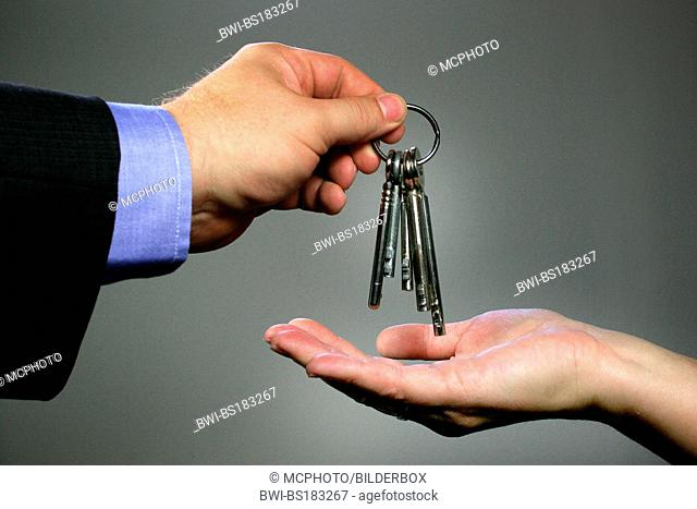 Two hands deliver keys