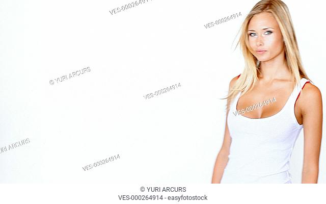 Lovely young blonde walking past a white background and waving coyly at the camera