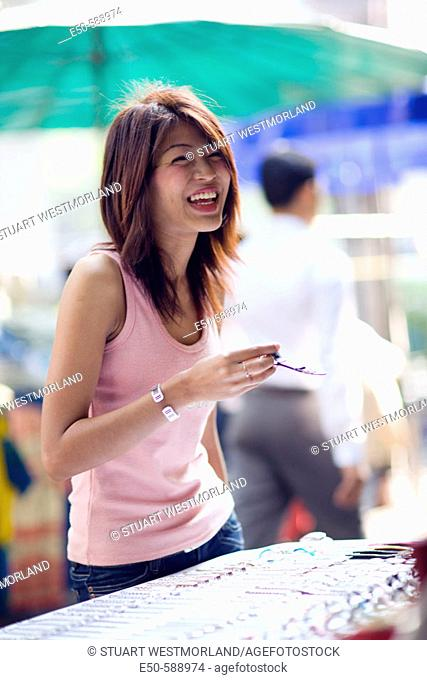 Thai woman (age 24) shopping in street market, Bangkok, Thailand