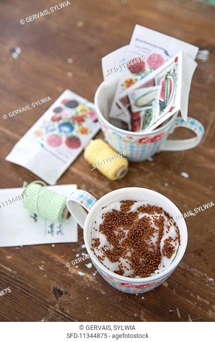 Cress seeds on cotton wool in a cup next to craft utensils and decorations