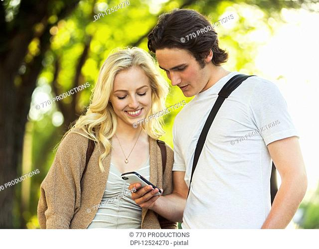 A young couple standing together and checking social media on a smart phone while walking through a university campus; Edmonton, Alberta, Canada