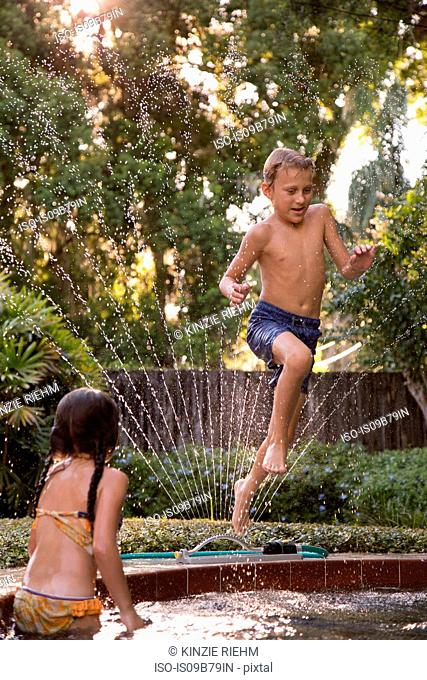 Young boy jumping into garden pool, mid-air