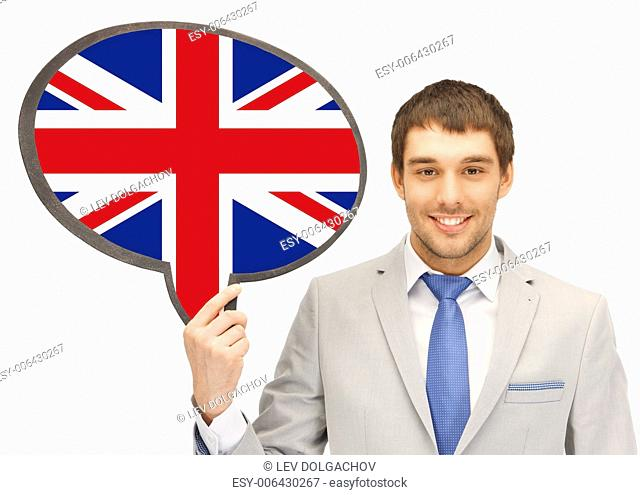 education, foreign language, english, people and communication concept - smiling young man or businessman in tie and suit holding text bubble of british flag