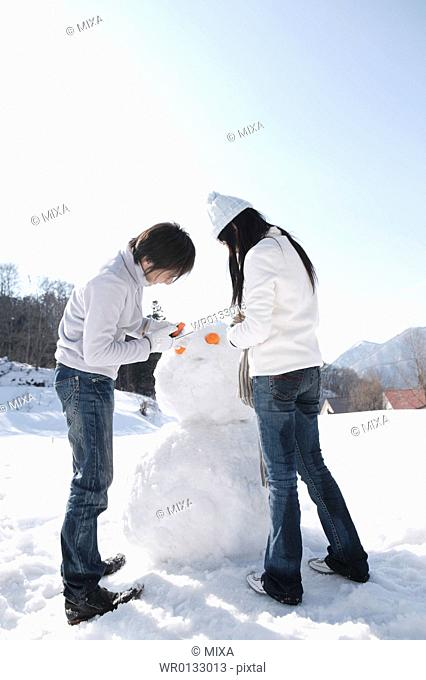 Young couple making snowman