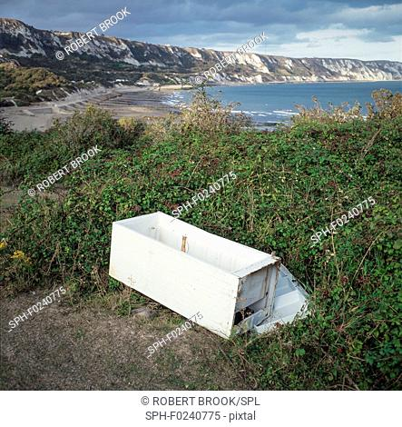 Dumped refrigerator and view of chalk cliffs between Folkestone and Dover, UK