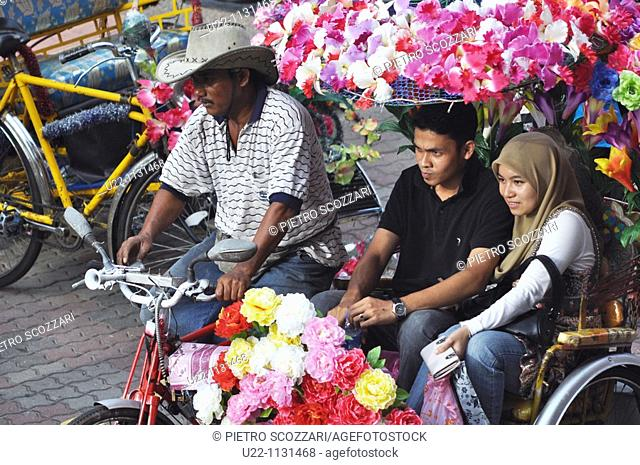 Malacca (Malaysia): a Malay couple touring around the city on a rickshaw in the Town Square