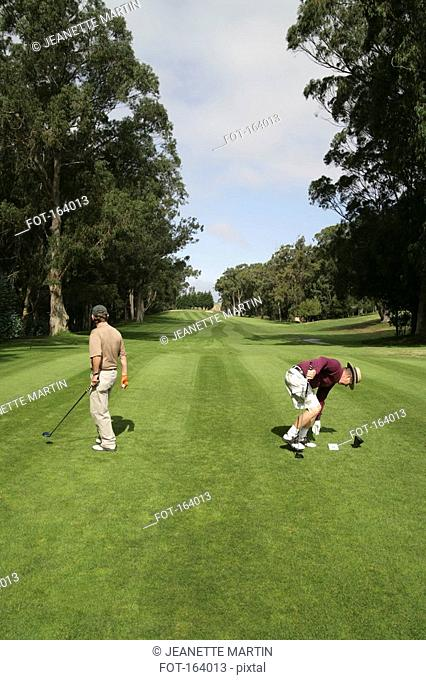 Two golfers on a tee box