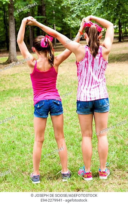 2 young sisters, side by side and backs to the camera, with their arms crossing, holding hands
