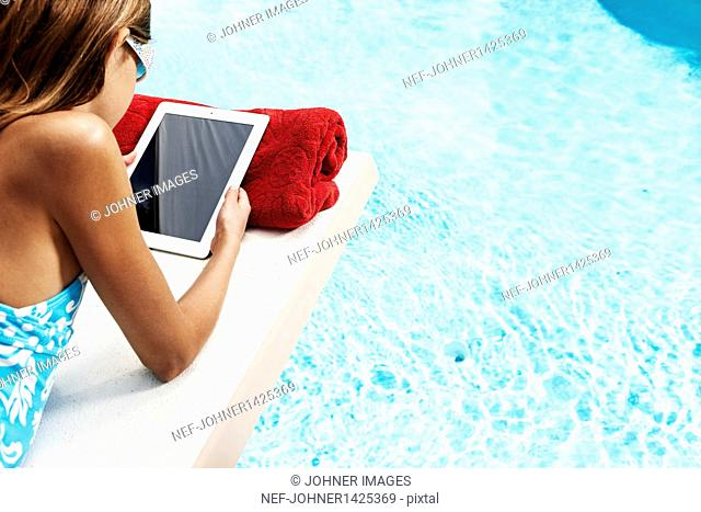 Girl with tablet pc on pool raft