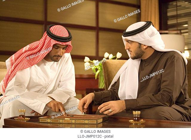 Two Arab Men Playing Backgammon in Living Room  Dubai, United Arab Emirates