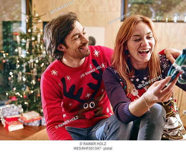 Happy couple unwrapping children's shoes in front of Christmas tree