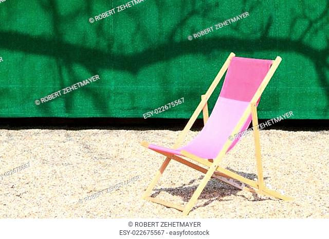 Folding Chair in front of green wall