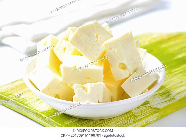 bowl of diced feta cheese on wooden cutting board - close up