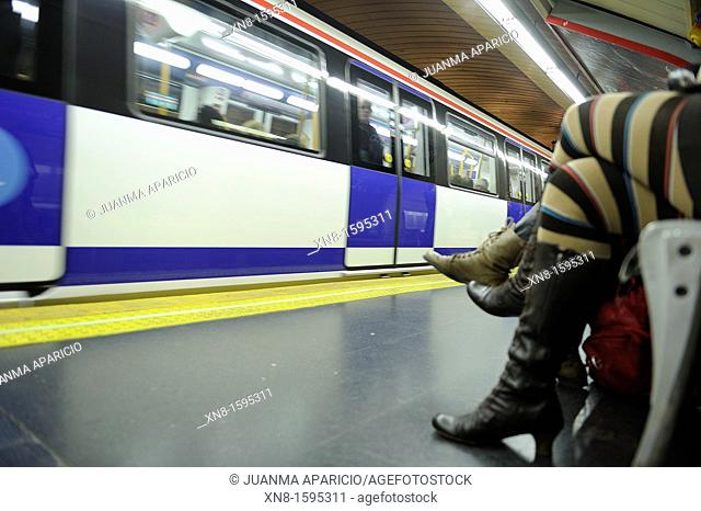 Two women sitting waiting for the subway